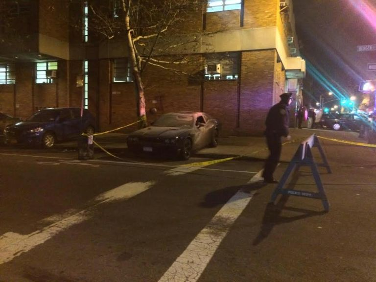 The car was parked on the sidewalk outside the 77th Precinct. It is unclear if it is a police vehicle, or if the incident is related to Eric Garner protests.