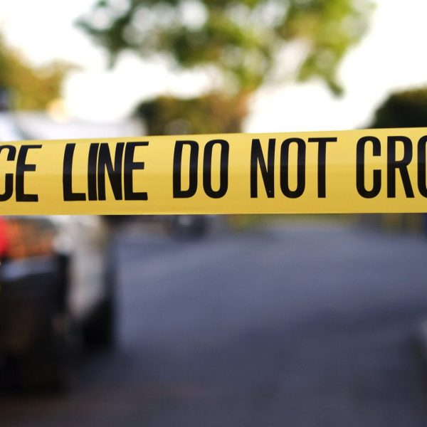 A blurred police car in the background behind yellow crime scene tape