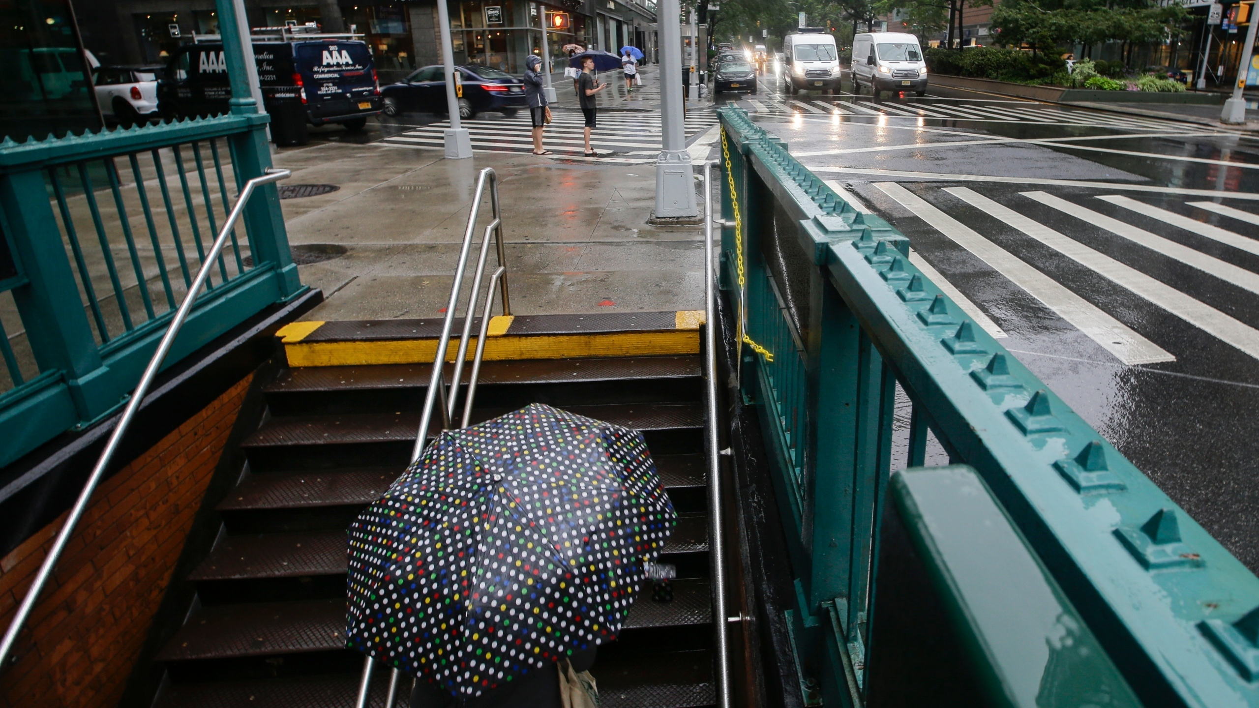Rain dampens nyc subway stairs as person with umbrella walks