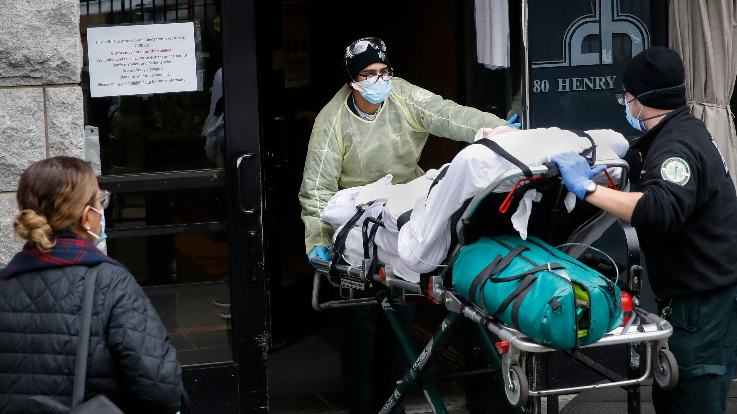 A patient is wheeled into Cobble Hill Health Center by emergency medical workers in Brooklyn