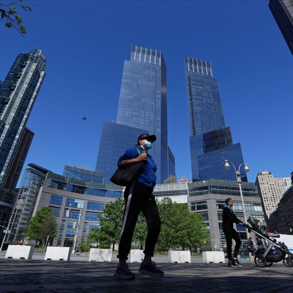 A woman wearing a protective mask walks near Columbus Circle Saturday, May 2, 2020, in New York. (AP Photo/Frank Franklin II)