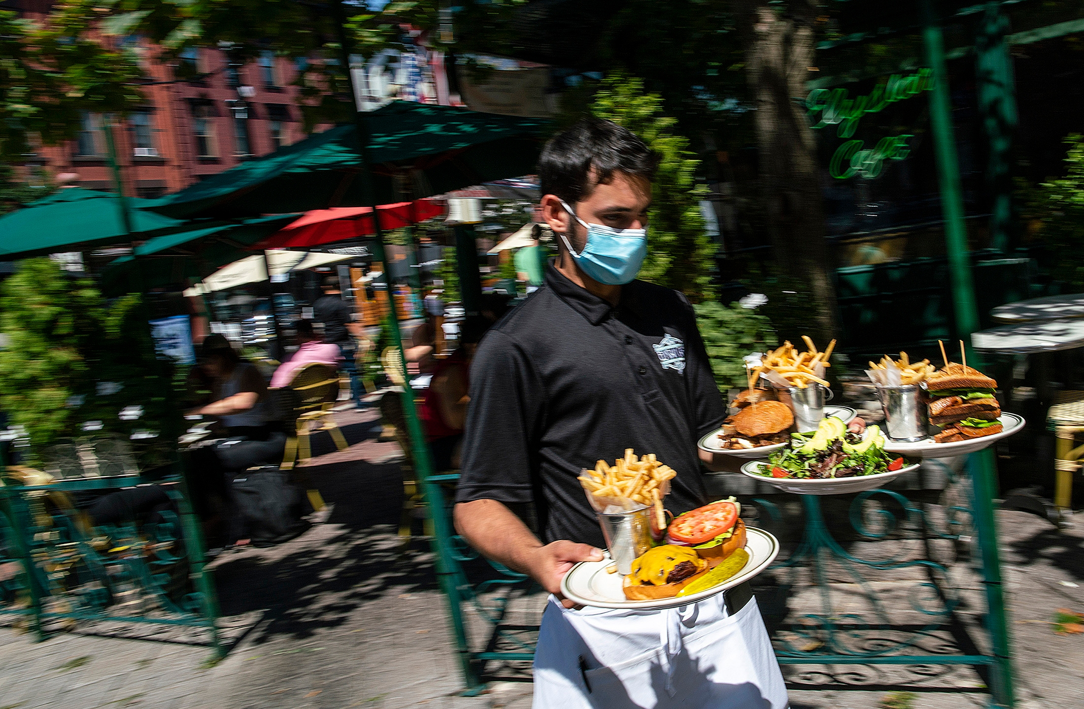 A waiter in a face mask delivers food to the tables outside of a local restaurant on Friday, Sept. 4, 2020, in Hoboken, New Jersey. (AP Photo/Eduardo Munoz Alvarez)