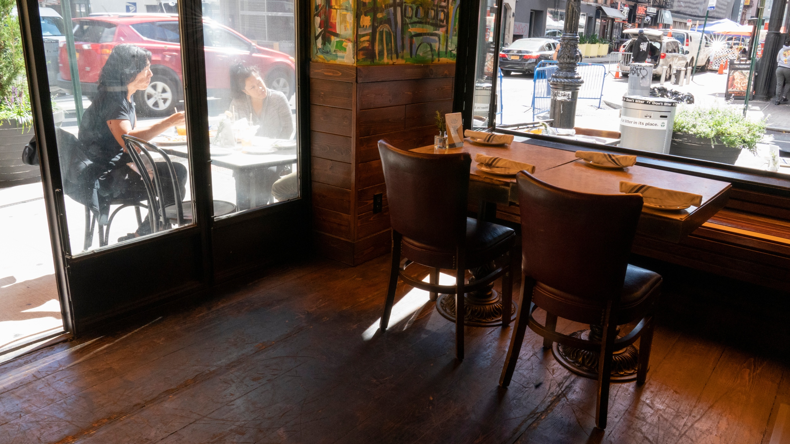 Customers dine outside a New York restaurant while an indoor table sits empty
