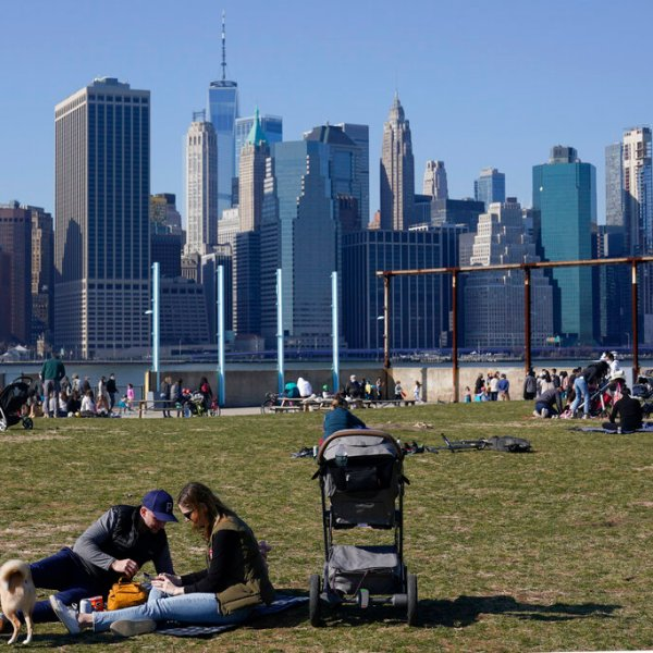 People enjoy the sunny weather and a view of the Manhattan skyline from the Brooklyn waterfront