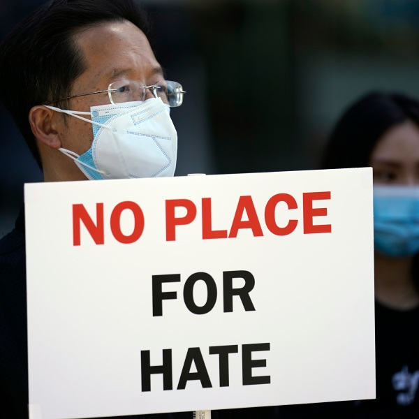 "A demonstrator's sign reads ""No Place For Hate"""