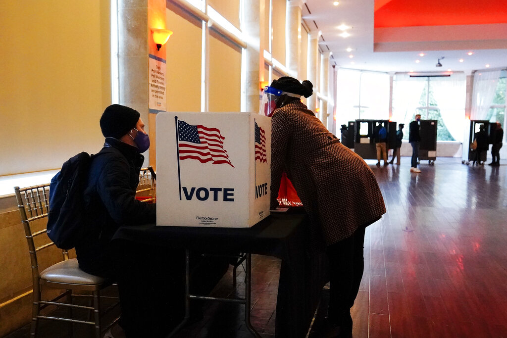A poll worker talks to a voter on Election Day on Nov. 3, 2020, in Atlanta