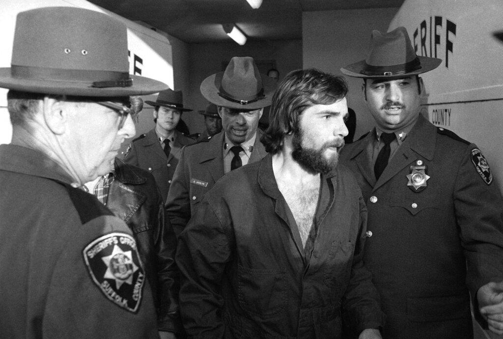 Ronald DeFeo Jr., accused in the Amityville murders, is led away in handcuffs by police