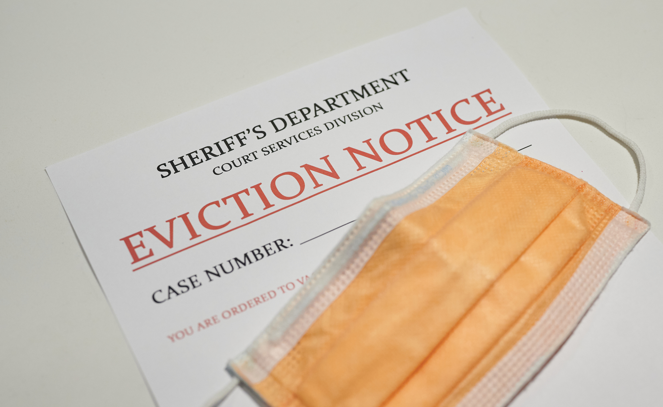 Yellow facial mask laying on top of the eviction note from sheriff's department