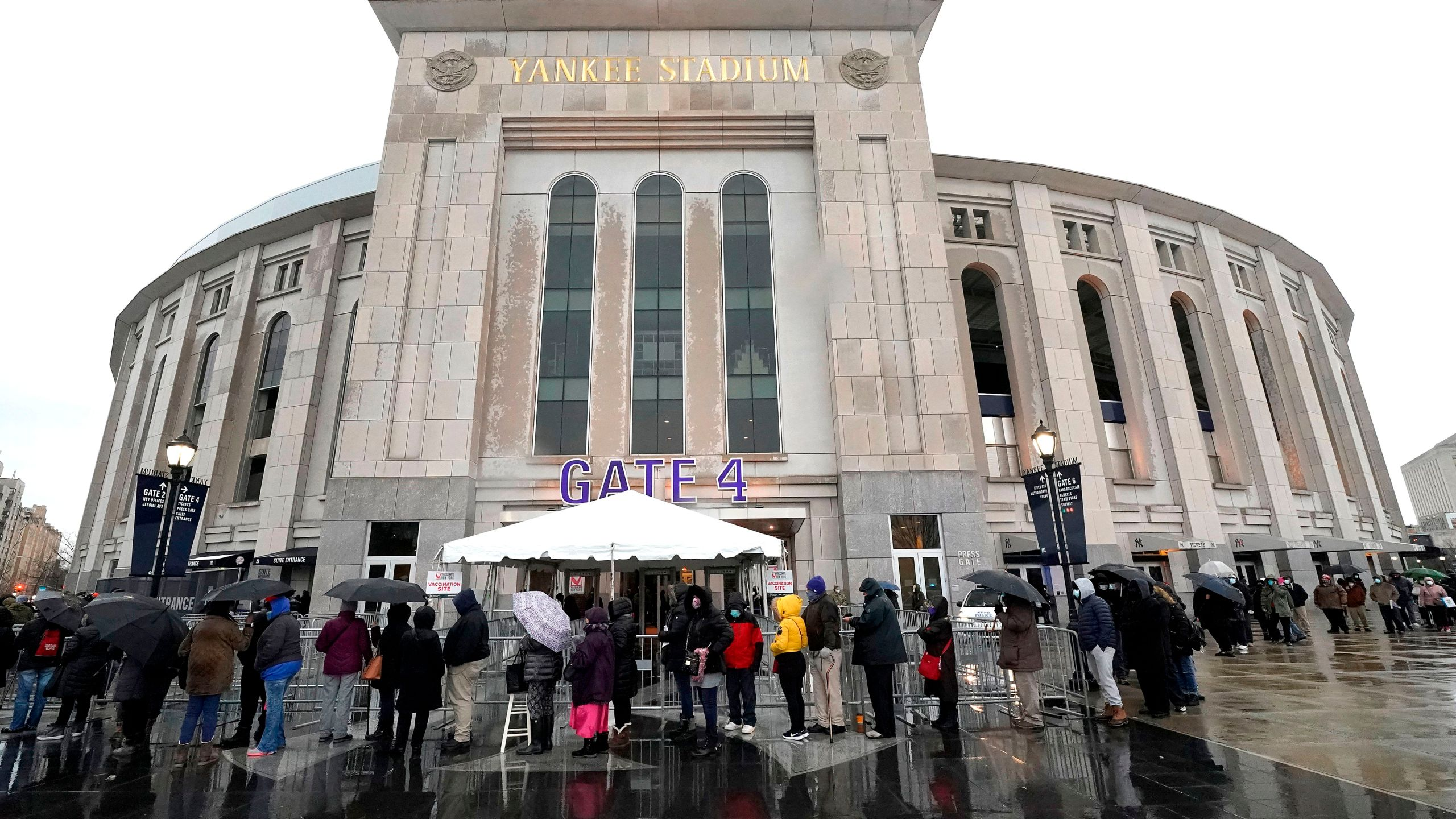 People line up in the rain outside the Yankee Stadium on February 5, 2021 in New York as the Stadium is turned into a mass Covid-19 vaccination site, which is strictly reserved for residents of The Bronx. (Photo by TIMOTHY A. CLARY / AFP) (Photo by TIMOTHY A. CLARY/AFP via Getty Images)