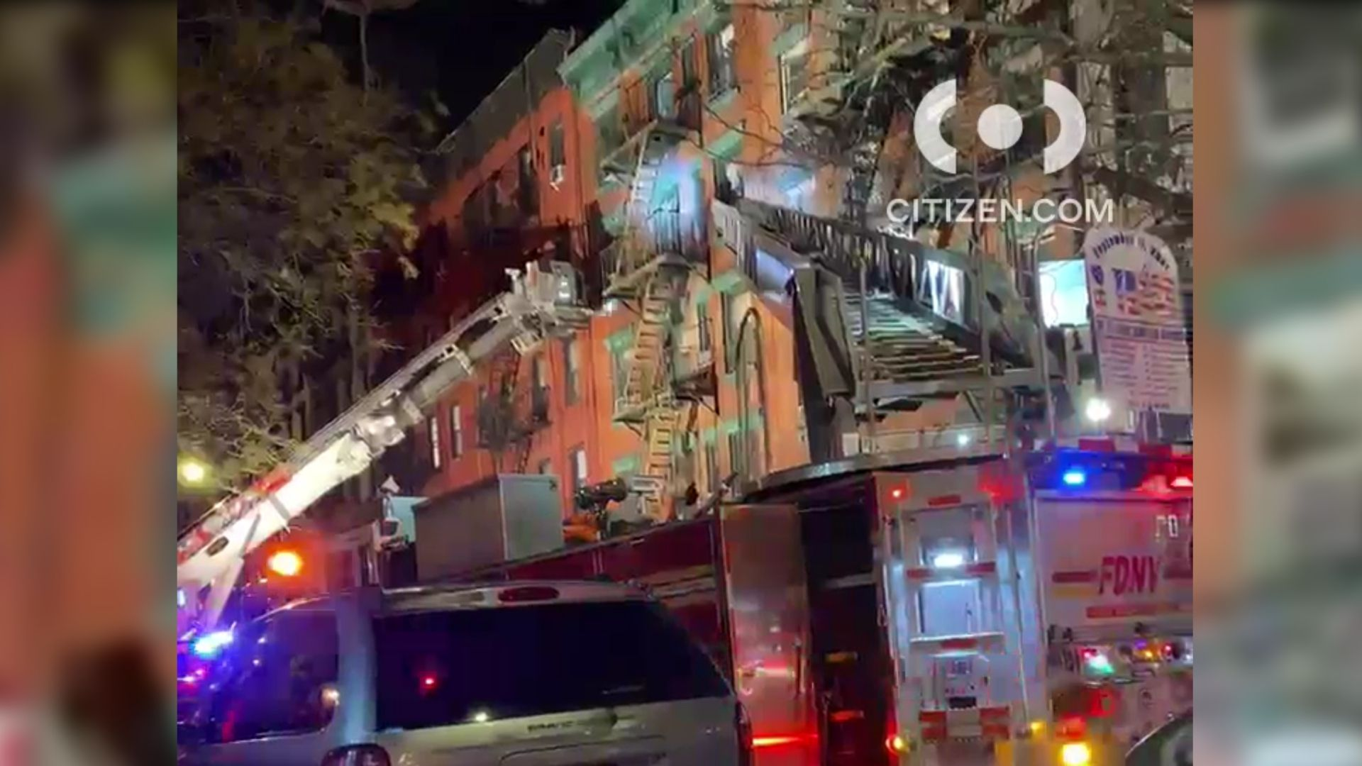 Firetruck ladders extend to a top-floor apartment in a fire in the East Village in Manhattan