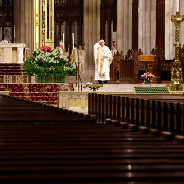A member of the clergy looks out over empty pews before the start of an Easter Mass at St. Patrick's Cathedral