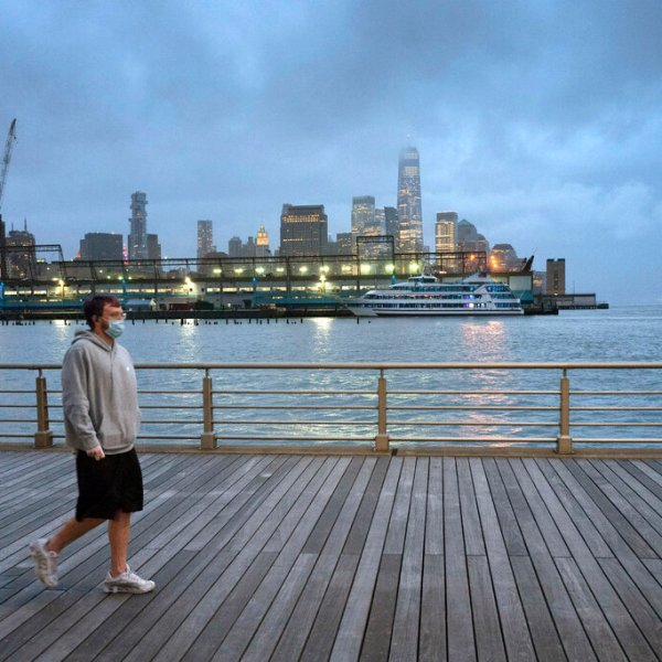 Man wearing a mask walks with the new york city skyline in the background