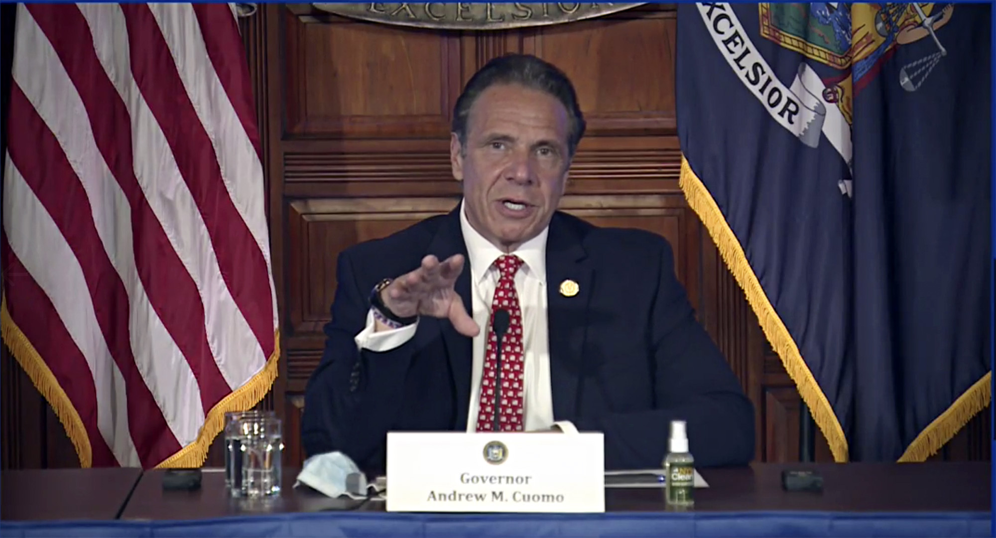 new york governor andrew cuomo speaks at a desk