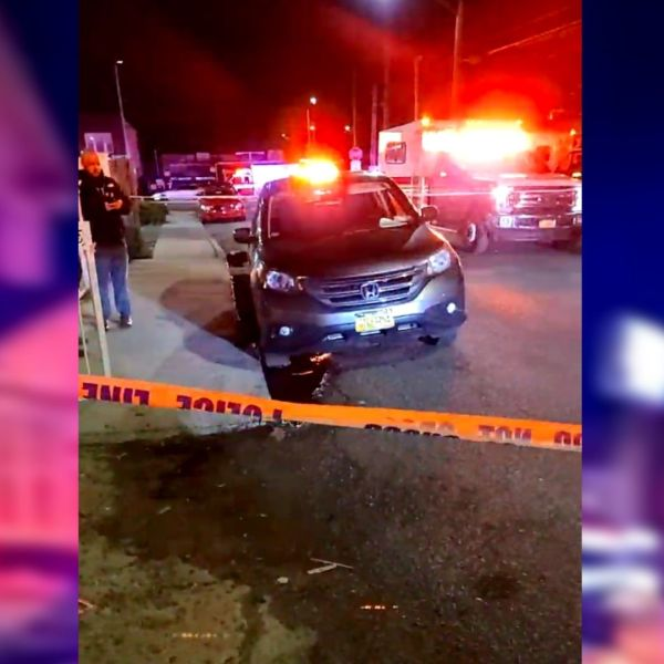 Police on the scene after a woman was shot in the stomach while sitting in her car in Queens