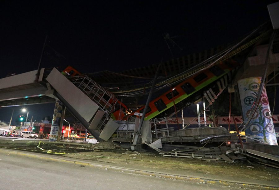 Mexico City's subway cars lay at an angle after a section of Line 12 of the subway collapsed in Mexico City, Tuesday, May 4, 2021. The section passing over a road in southern Mexico City collapsed Monday night, dropping a subway train, trapping cars and causing at least 50 injuries and several dead, authorities said.