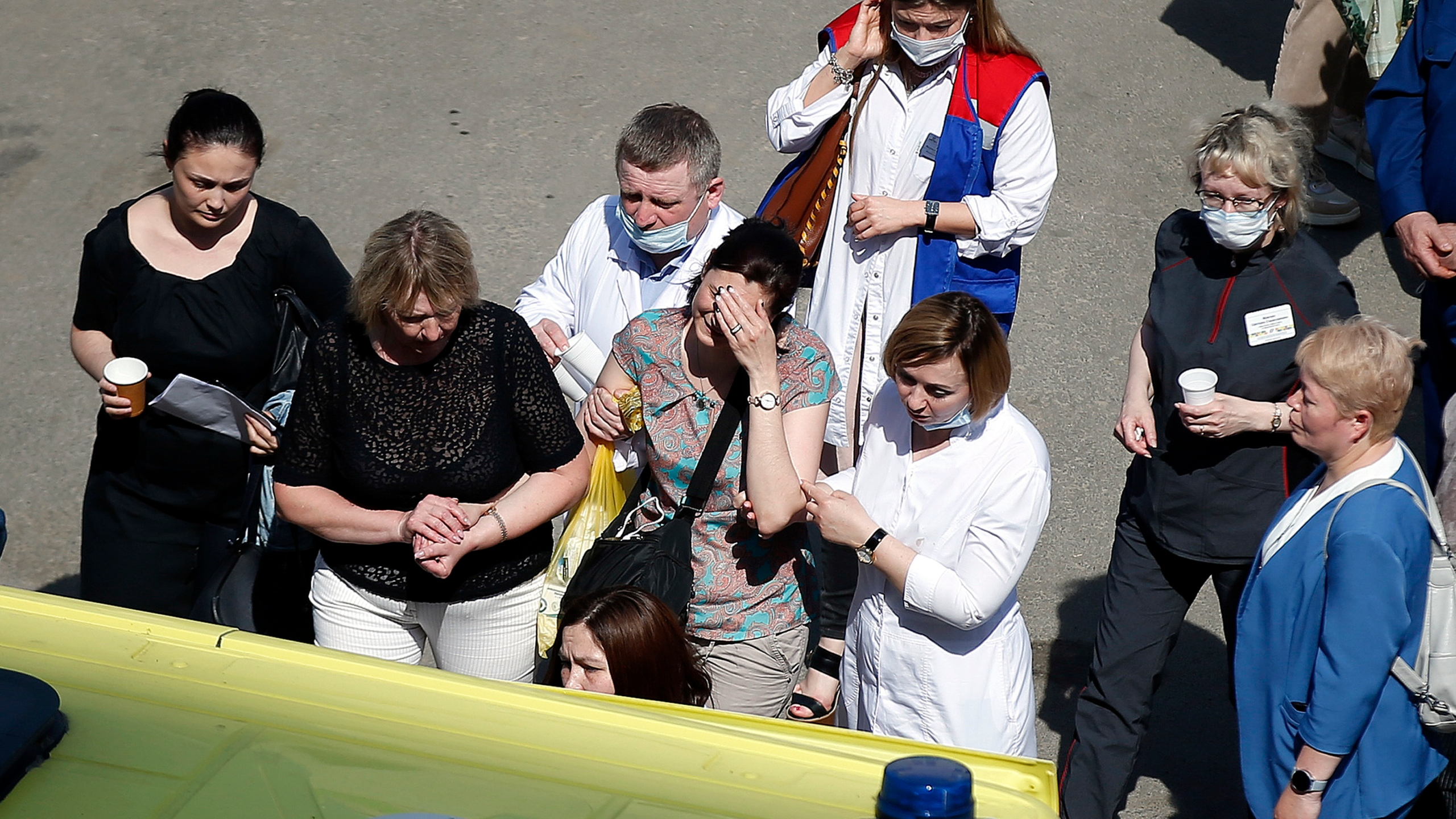 Medics and friends help a woman board an ambulance at a school after a shooting in Kazan, Russia, Tuesday, May 11, 2021.