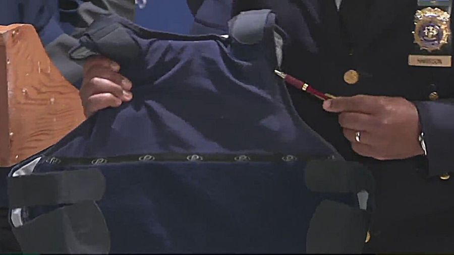 NYPD officials hold up an officer's vest at a press conference Thursday, May 13, 2021 after the officer was shot three times in a shootout with a suspect in Brooklyn the night before